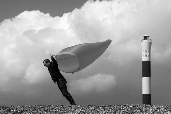 A man lies exhausted on the ground on a hillside, the wind funnel is empty and flapping around.